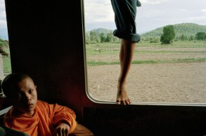 Cambodia. Train between Battambang and Phnom Penh. Young monk in train and passenger  climbing to travel on the roof.