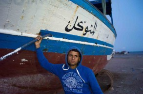 Zarzis, Tunisia, April 2011. Ali Ghommidh, 19, is posing in front of the boat which was supposed to take around one hundred illegal immigrants, including him, one week ago, but broke down and was finally rescued by the Tunisian Marine. Ali has failed six times leaving Zarzis but was reimbursed each time by the trafficker and will try again. © Patrick Zachmann/Magnum Photos