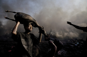 A young worker carries the carcass of a freshly killed goat to be roasted by the flames of burning tires at the Trans Amadi abattoir of Port Harcourt, the capital of the Rivers state, Nigeria on June 22, 2006. The slaughterhouse maintains deplorable conditions, lacking organization and basic hygiene. The animals are killed in the open, their blood spilling into the waterways below, and their skins burned by the flames of old tires, creating thick clouds of black smoke over neighboring residential villages.