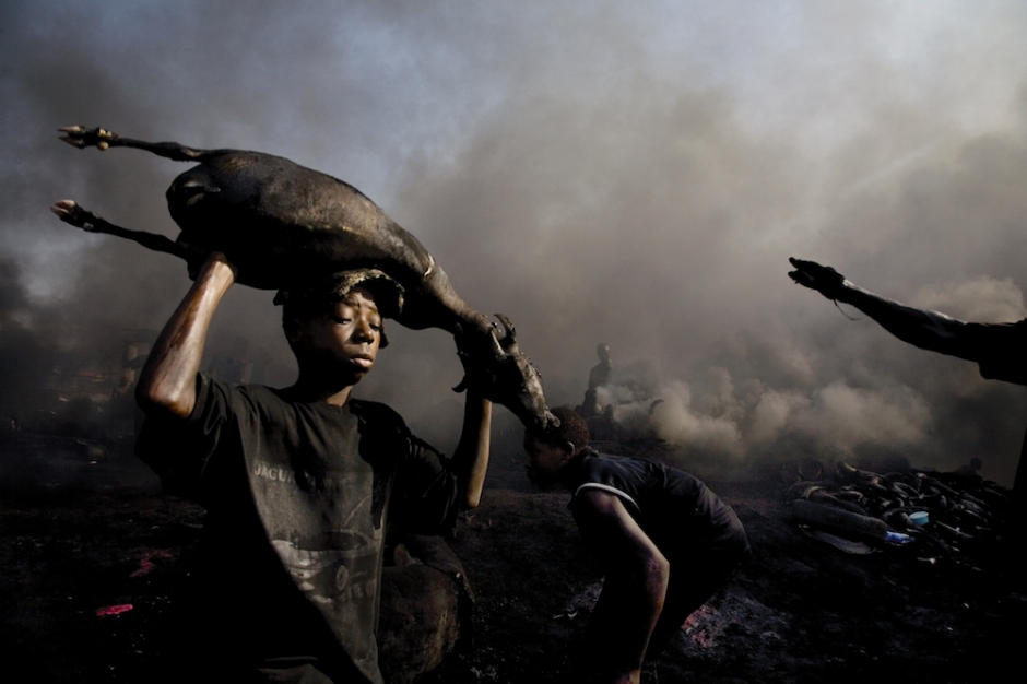 A young worker carries the carcass of a freshly killed goat to be roasted by the flames of burning tires at the Trans Amadi abattoir of Port Harcourt, the capital of the Rivers state, Nigeria on June 22, 2006. The slaughterhouse maintains deplorable conditions, lacking organization and basic hygiene. The animals are killed in the open, their blood spilling into the waterways below, and their skins burned by the flames of old tires, creating thick clouds of black smoke over neighboring residential villages. © Ed Kashi / VII Photo