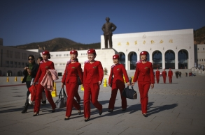 "An all girls group of Young Communist League members walks past a statue of Chairman Mao Zedong in front of the Yan'an Revolutionary Memorial Hall in Yan'an, China on Nov. 7, 2009. Yan'an is promoted as the ""Revolutionary Holy Land"" and offers a number of museums, monuments and other ""Red Tourism"" sites supported by the Chinese government."